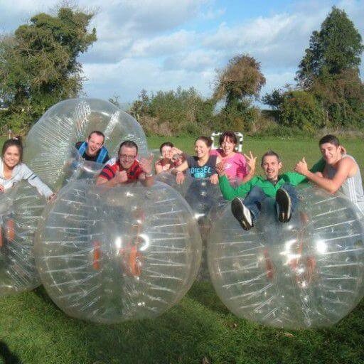 An extended family of adults and children pose for a photo with bubble balls during a bubble soccer match.