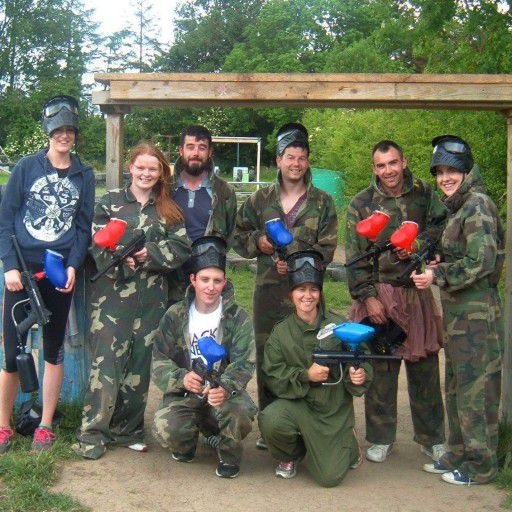 A team building group of eight dressed in camouflage gear and holding paintball guns pose for a photo after a game of paintball.