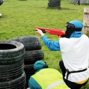 One paintball player is hunkered down and shooting a splatball gun while another is hiding behind a tyre obstacle on the paintball arena. A third player is hiding in the background with a paintball gun.