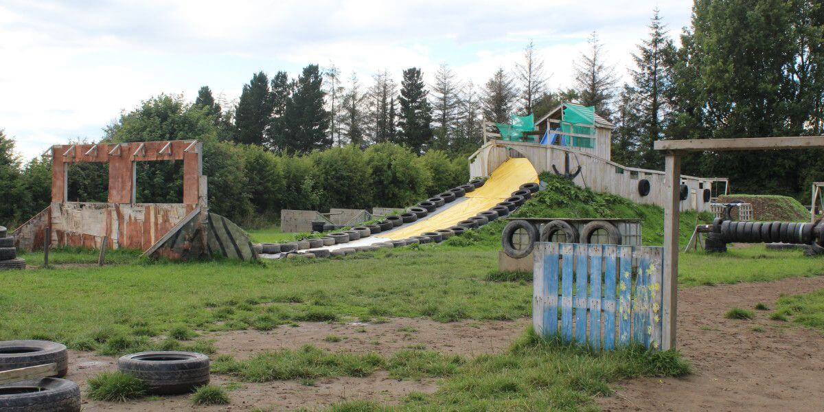 Wooden obstacles and tyres with a water slide forming a military style assault course