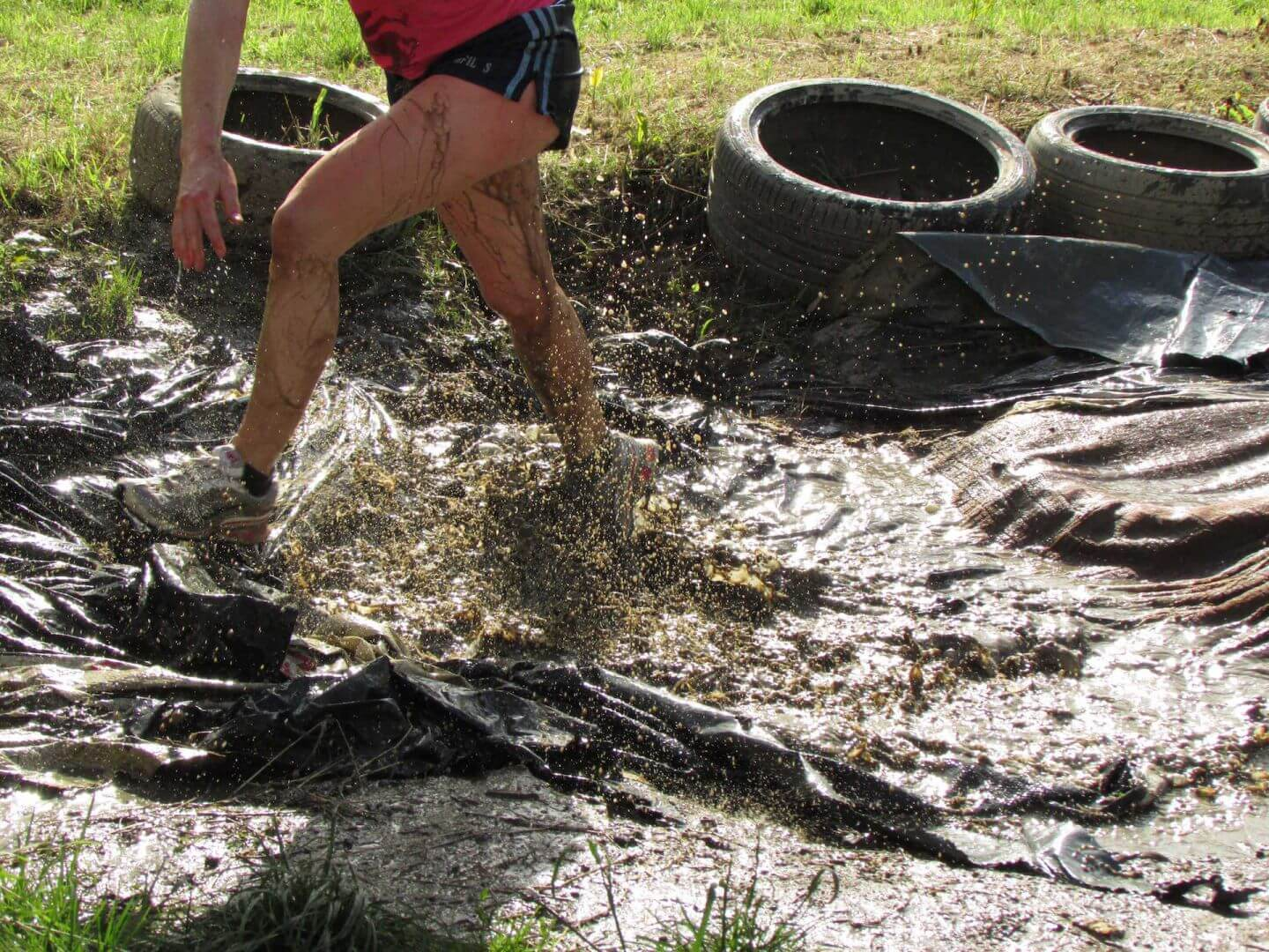 A person walking through muddy water on the assault course.
