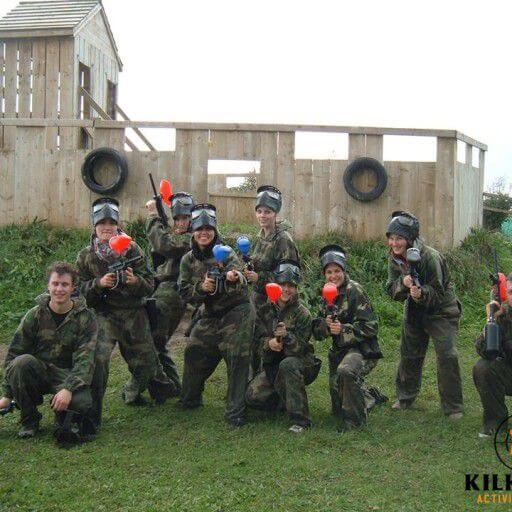 A group of nine people in camouflage posing with paintball guns and wearing paintball masks.