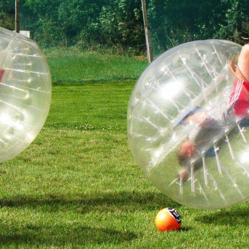 One player flips over during a Bubble Soccer game in Kilkenny Activity Centre while tow other buble soccer players look on..