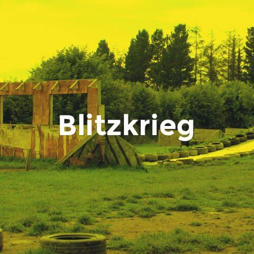 A paintball arena with tyres and trenches overlayed with the word Blitzkrieg.