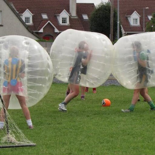 Three players playing Bubble Soccer, each wearing a large bubble ball.