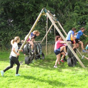 A group of girls climbing over a tyre and timber obstacle during a hen party arranged by Kilkenny Hen Parties.