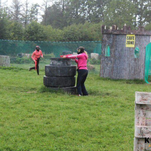 A girl on a hen party wearing a mask and shooting a Splatball gun from behind a tyre obstacle while another girl with a Splatball gun runs through the paintball arena in the background.