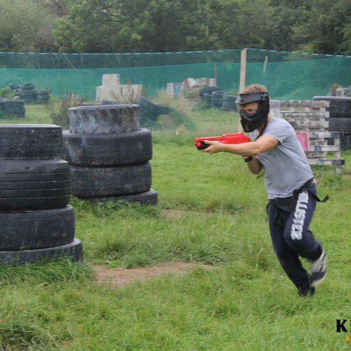 Stag Party Kilkenny A boy shooting a splatball gun and wearing a safety mask runs through a paintball arena with tyre walls and timber obstacles.