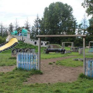 Timber and tyre obstacles forming the Kilkenny activity centre assault course with the renowned water slide to the rear of the photo.