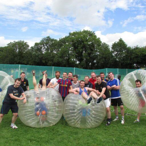 Stag Party Kilkenny A corporate group posing for a photo after a bubble soccer game with four of them in bubble balls.