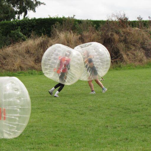 Two bubble soccer players tackle each other during a bubble soccer match