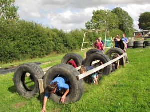 Hen Parties Kilkenny A group of girls on a hen party crawl through a tyre obstacle whilst others watch.