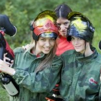Three girls in camouflage gear pose with paintball guns and masks.