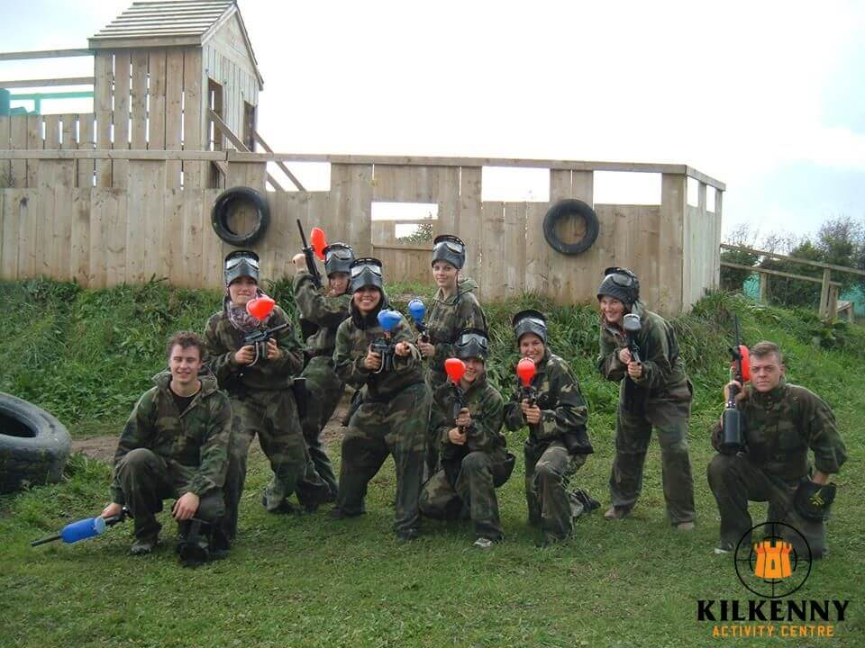 Nine people dressed in camouflage gear and wearing masks pose for a photo with their paintball guns.
