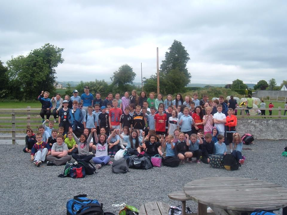 A large group of students sitting and standing in the Kilkenny Activity Centre Car Park after completing school tour activities.