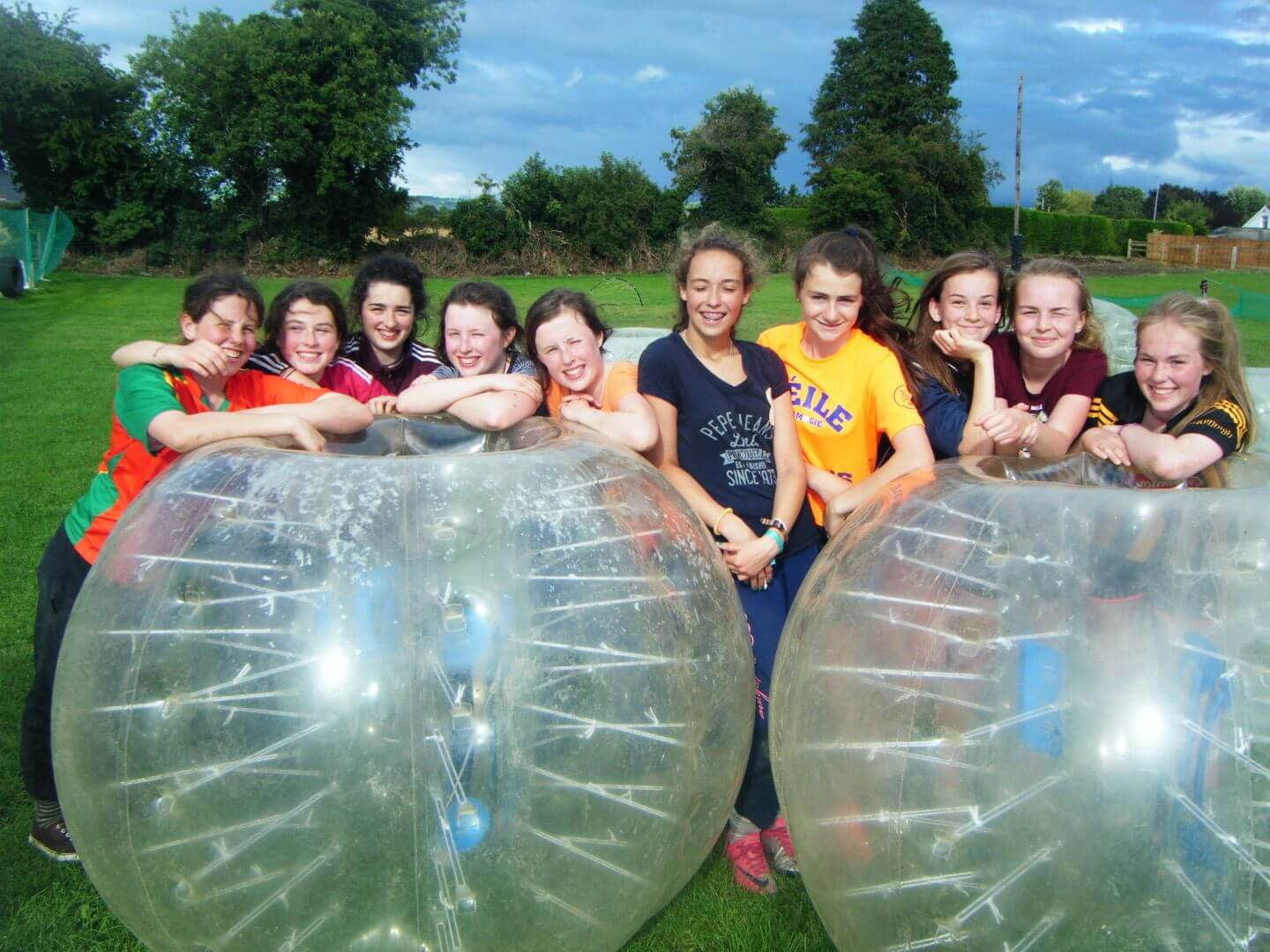 A group of happy girls on a birthday party posing behind two large bubble balls whilst taking a break during a bubble soccer game.