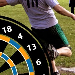 A man kicking a ball during a game of Foot Darts with a large dart board in the foreground.