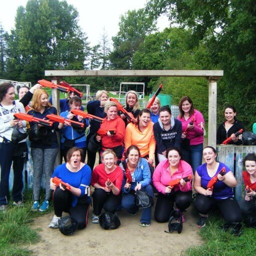 A hen party of twenty ladies pose with Splatball guns after taking part in a Splatball game.