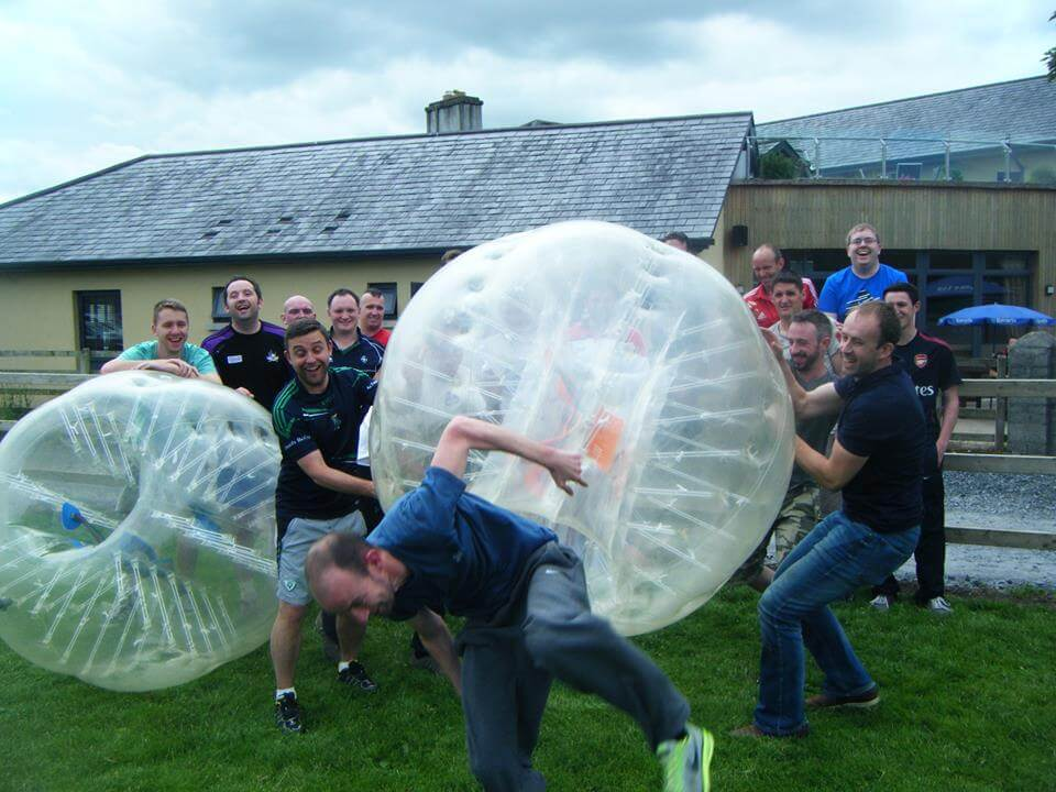 Two men try to put a bubble ball over another man's head while taking part in bubble soccer during a stag party.