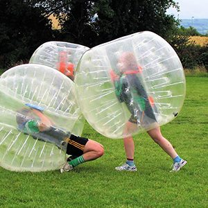 Three players in bubble balls while playing bubble soccer. One is on the ground.