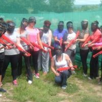 A group of ladies holding splatball guns after taking part in a splatball hen party arranged by Hen Parties Kilkenny.