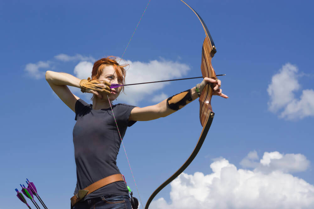 A girl using a bow and arrow during a hen party activity with Hen Parties Kilkenny
