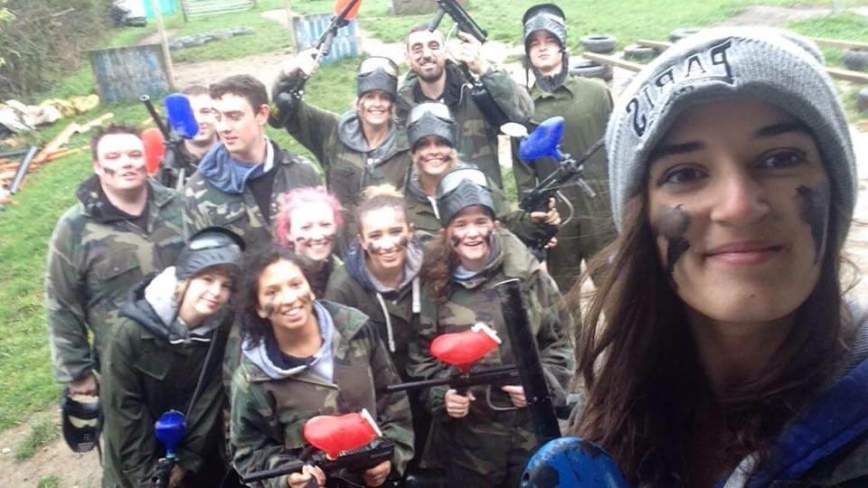 A group of girls wearing camouflage overalls and holding paintball guns posing for a selfie after taking part in paintball.