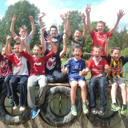 A group of boys posing for a photo and cheering after completing the assault course.
