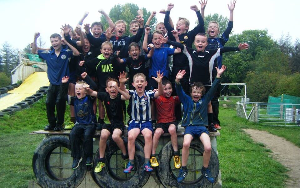 A group of young boys posing for a photo and cheering whilst standing on an obstacle