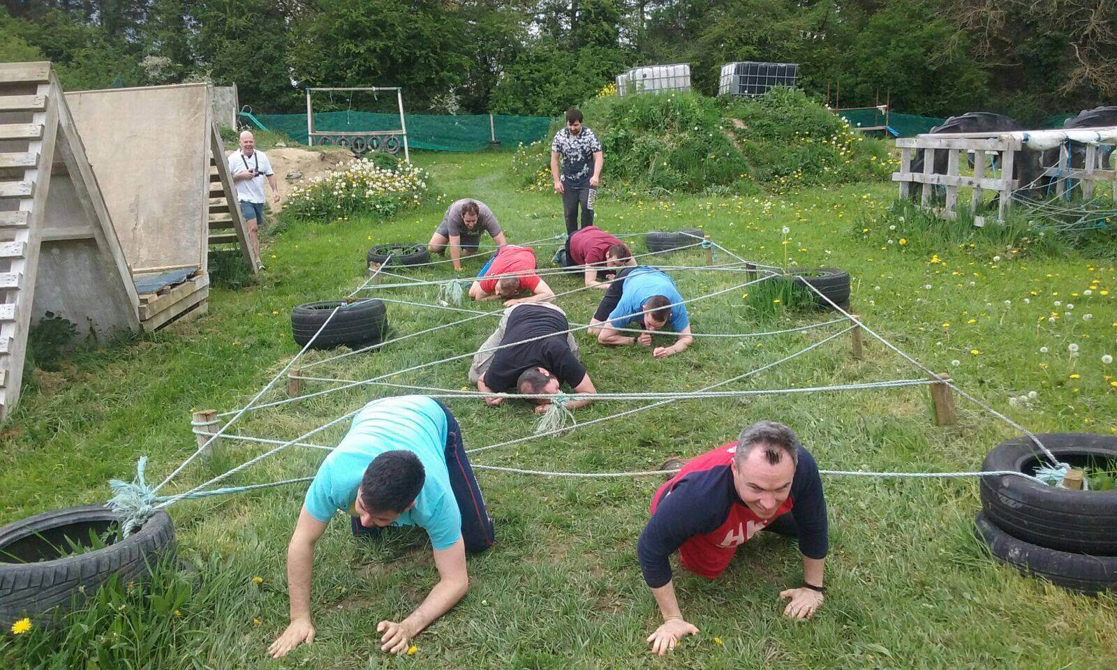A stag party crawling under criss-crossed ropes while taking part in the Assault Course