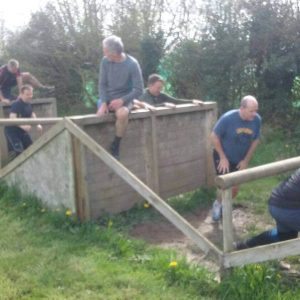 A stag party climbing wooden walls and ducking under beams while taking part in the Assault Course.
