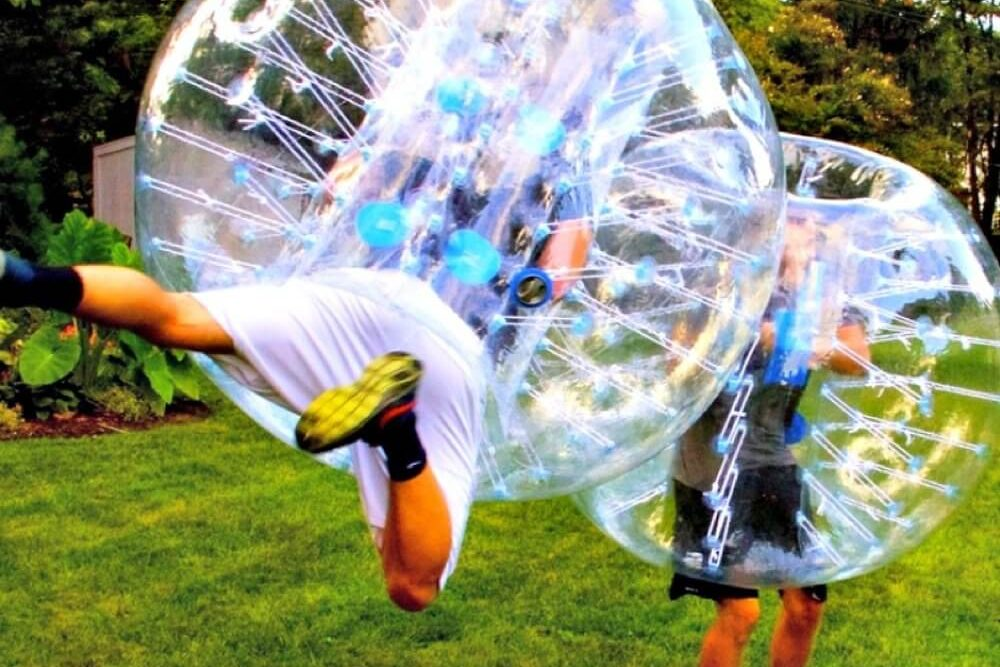 Two men collide while playing bubble soccer. One is in the air as if flying.